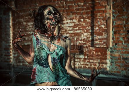Horrible bloody zombie girl standing outdoor by the brick wall. Halloween.