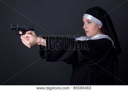 Portrait Of Young Woman Nun Shooting With Gun Over Grey