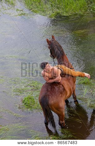 Young Sexy Man With A Naked Torso Lies On Grain Of The Horse Standing In The River