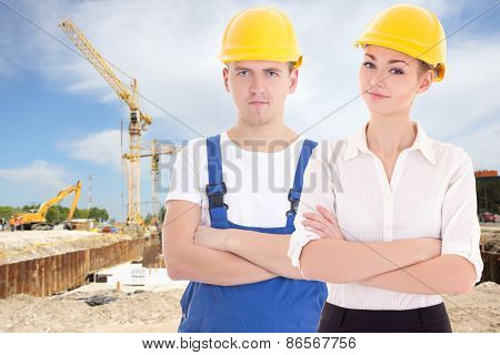 Young Man Builder And Business Woman Architect In Helmet