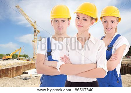 Team Work Concept - Two Young Women And Man In Blue Builder 's Uniform