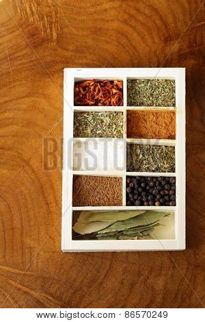 set of different spices (pepper, salt, turmeric, bay leaves, chili, herbs) in a wooden box