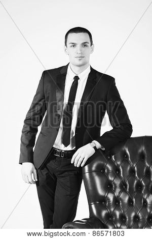 Male businessman stands near the chair leather chair