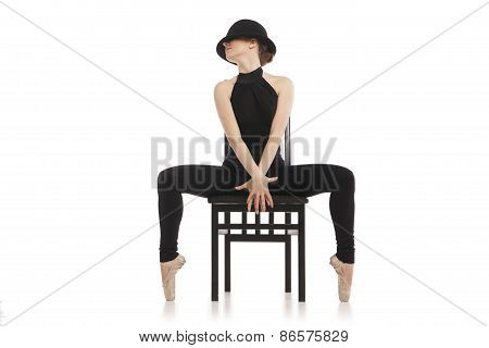 Pretty young ballerina sitting on the chair