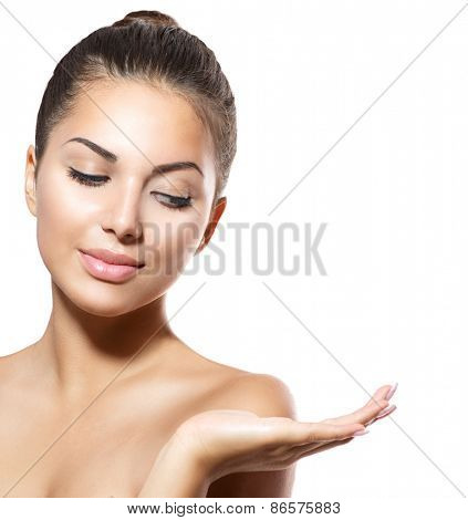 Beauty Woman Portrait. Beautiful Spa Girl showing empty copy space on the open hand palm for text. Proposing a product. Gestures for advertisement. Isolated. Fresh Clean Skin. Skin Care Concept