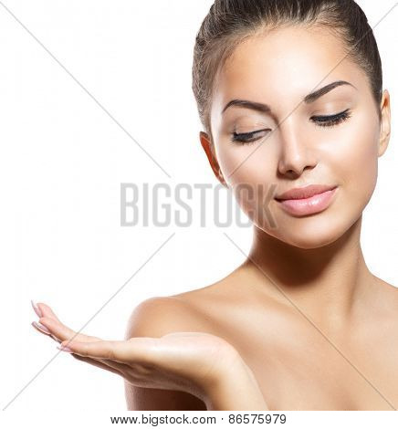 Beauty Woman Portrait. Beautiful Spa Girl showing empty copy space on the open hand palm for text. Proposing a product. Gestures for advertisement. Isolated. Fresh Clean Skin. Skin body Care Concept