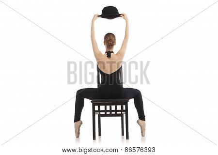Back view of pretty young ballerina sitting on the chair. Isolated