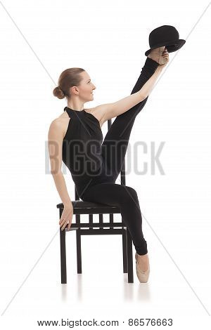 Pretty young ballerina sitting on the chair. Isolated
