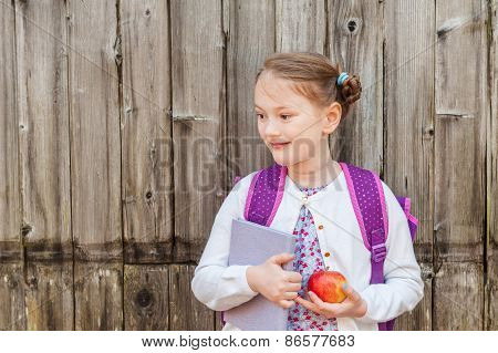 Outdoor portrait of a cute little girl of 7 years old, wearing backpack