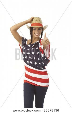 Pretty young American girl showing ok sign, wearing American flag t-shirt and straw hat, smiling happy.