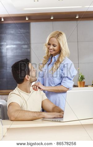 Young man sitting at table at home, using laptop computer, woman touching shoulder, smiling.