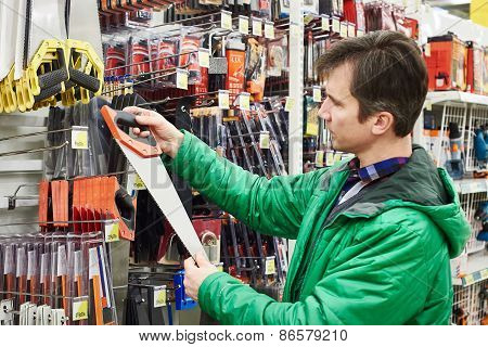 Man Buying Handsaw In Store