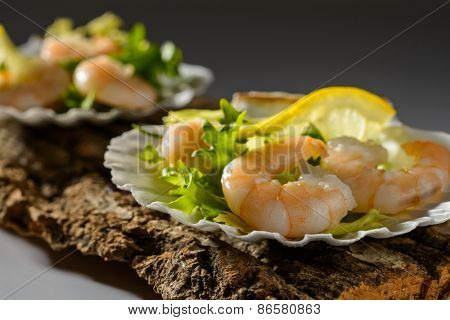 Close up of prawn salad with lemon in shells with creative lighting