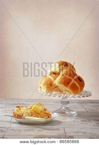 Serving of hot cross bun with butter curl