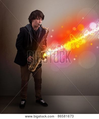 Attractive young man playing on saxophone with colorful sound waves
