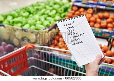 Shopping List In Hands Of Woman In Supermarket