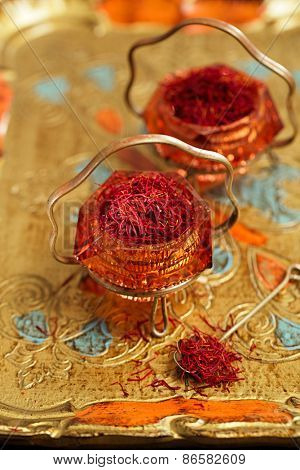 saffron spice in antique vintage glass bowl, closeup