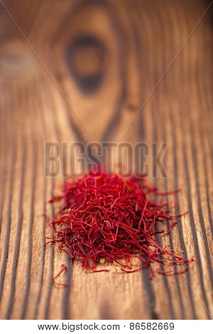 saffron spice in pile on old textured wooden background, closeup