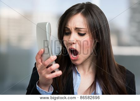 Portrait of an angry businesswoman yelling at phone