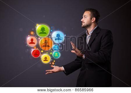 Young businessman holding colorful social network icons in his hand