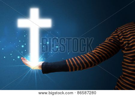 Young woman holding a glowing cross in her hand