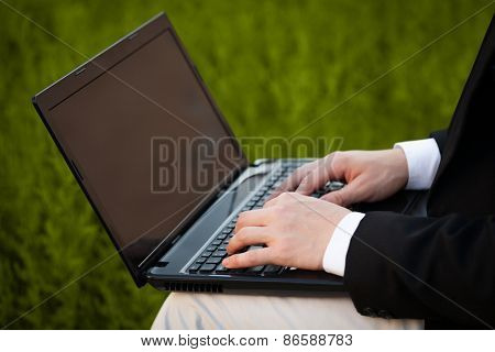 Businessman pressing modern laptop computer on colorful office background