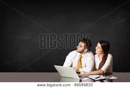 Business couple sitting at black table with a laptop on black background