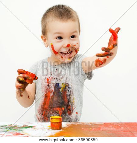 little boy playing with paints