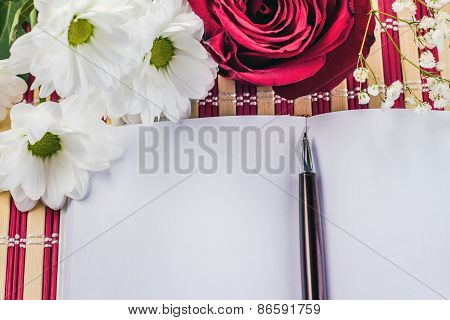 white paper sheet and bouquet of red roses and white daisy