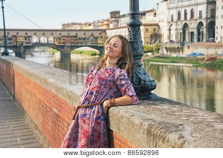 Relaxed Young Woman On Embankment Near Ponte Vecchio In Florence
