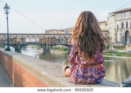 Young Woman Sitting Near Ponte Vecchio In Florence, Italy. Rear