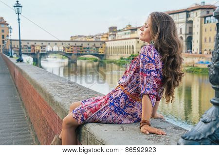 Relaxed Young Woman Sitting Near Ponte Vecchio In Florence, Italy