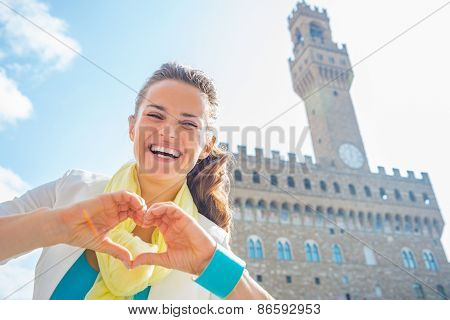 Happy Young Woman Showing Heart Gesture Shaped Hands In Front Of