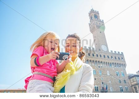 Happy Mother And Baby Girl Checking Photos In Camera In Front Of