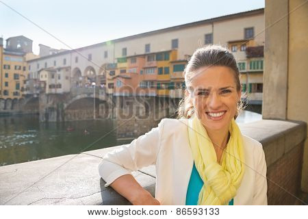 Portrait Of Smiling Young Woman Near Ponte Vecchio In Florence,