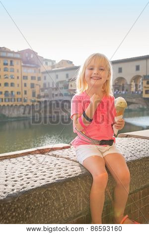 Portrait Of Happy Baby Girl Eating Ice Cream Near Ponte Vecchio In Florence, Italy