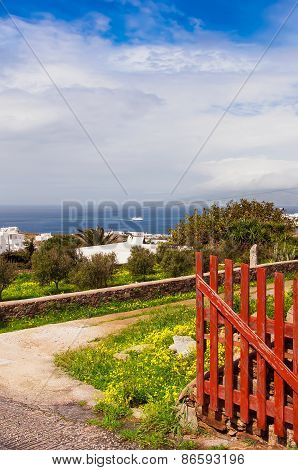Old Red Wooden Gate Into The Courtyard Village House On A Background Of Sea And Sky With Clouds.