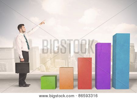 Business person climbing up on colourful chart pillars concept on city background