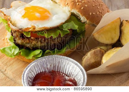 Burger With Fried Egg And Roasted Potato Wedges