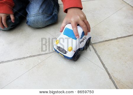 Boy Playing With Toy Police Car