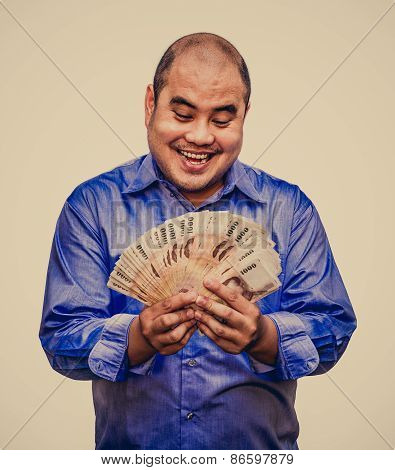 An Office Guy Holding Pile Of Thai Banknotes With His Greedy Face Sweating In Grunge Vintage Atmosph