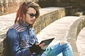 stock photo of dreadlocks  - freelancer guy with dreadlocks sitting on staircase with digital tablet typing message warm filter applied - JPG