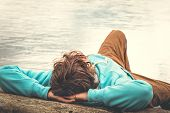 foto of wild adventure  - Young Man laying relaxing outdoor with lake on background Lifestyle Travel concept - JPG
