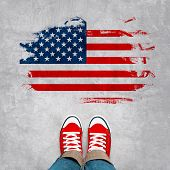 foto of citizenship  - American Urban Youth Concept Feet in Red Sneakers from Above Standing in front of Grunge USA Flag - JPG