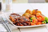 stock photo of roasted pork  - Pork Chop Sunday Lunch With Onion Gravy - JPG