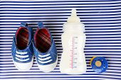 stock photo of nipple  - Baby shoes with nipple and bottle of milk on blue background - JPG