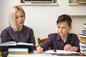 pic of students classroom  - Young student learns at home with a his mom tutor - JPG