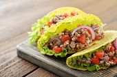 image of tacos  - Mexican tacos with meat onion and tomato on plate on wooden background - JPG
