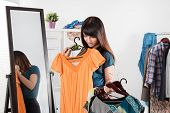 pic of dress-making  - Beautiful young woman near rack with clothes making chioce - JPG