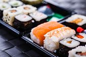 foto of sushi  - a sushi box or bento box with assorted sushi pieces over a dark black lunch mat - JPG